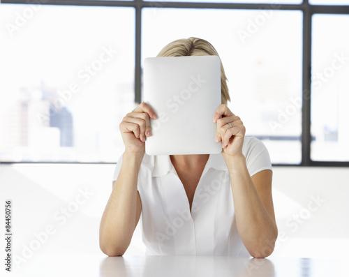 Fotografía  Businesswoman Sitting At Desk In Office With Face Hidden Behind Digital Tablet
