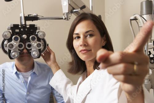 Fotografía  Female Optician In Surgery Giving Man Eye Test