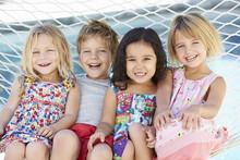 Four Children Relaxing In Garden Hammock Together