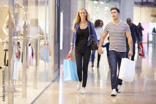 Plakat Szczęśliwej pary przewożących torby w centrum handlowym
