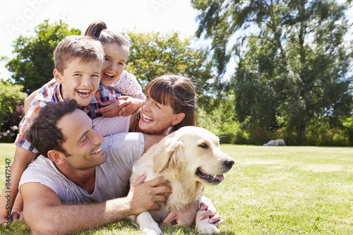 Foto  Family Relaxing In Garden With Pet Dog
