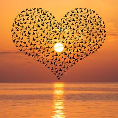 Naklejka Na szklane drzwi i okna Beautiful sunset with birds flock in heart shape above sea