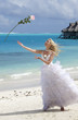 The happy bride in a white long dress throws up a rose on a beach on background of the sea ..