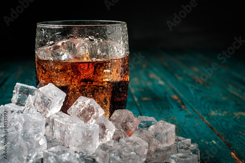 Glass of cola with ice on a wooden table.