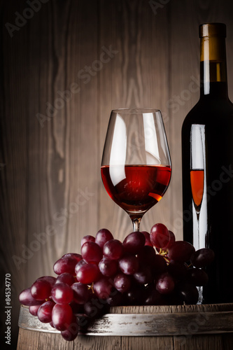 Detail of bottle and glass of red wine with grapes