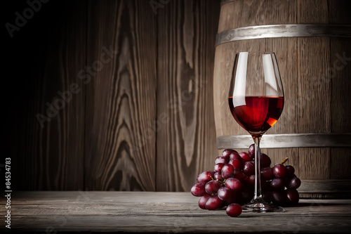 Glass of red wine with grapes and barrel Canvas Print