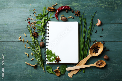 Photo Stands Herbs 2 Open recipe book with fresh herbs and spices on wooden background