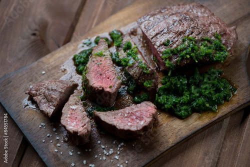 Medium rare grilled beef steak with chimmichurri sauce, close-up Poster