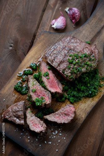 Medium rare beef steak with chimichurri on a cutting board Poster