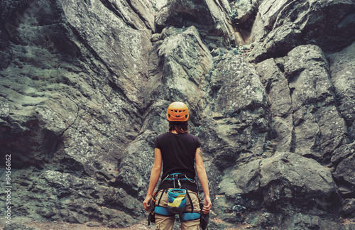 Alpinisme Climber woman standing in front of a stone rock outdoor