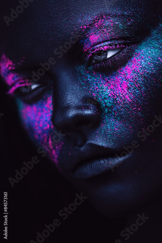 portrait of woman in black paint and neon powder