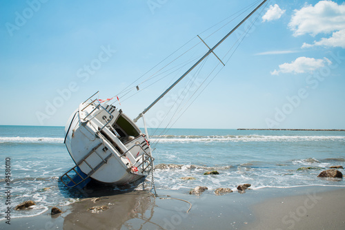 sailboat wrecked and stranded on the beach Canvas Print