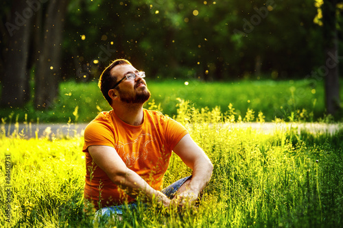 Photo  A happy thoughtful dreamer man is sitting on green grass
