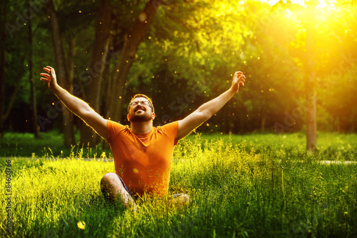 A happy man is relaxing on green grass with squint eyes
