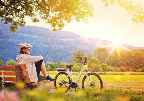 Fotomural  La mujer de relax junto a su bicicleta eléctrica - electrónica de potencia 05