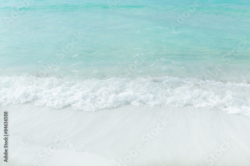 Fragment of view of closeup white sand beach and turquoise ocean background Wallpaper Mural