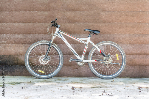 Mountain bike leaning against a wooden wall. © tapui