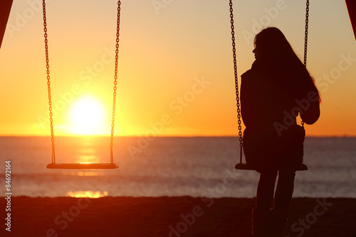 Fotografie, Obraz  Single woman alone swinging on the beach