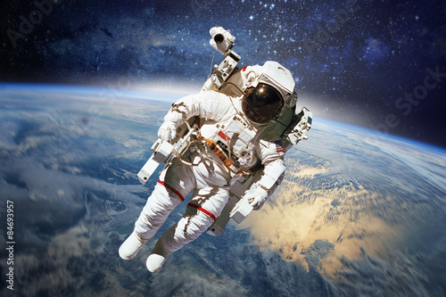 Spoed Foto op Canvas Heelal Astronaut in outer space with planet earth as backdrop. Elements