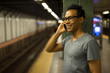Young African Asian man in New York City at night talking cell phone in subway