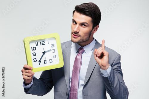 Businessman holding clock Canvas Print