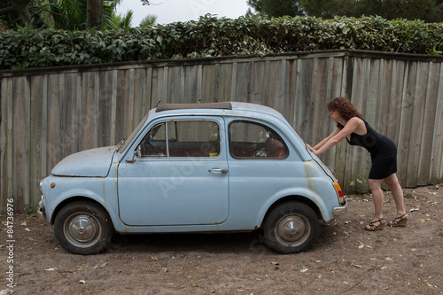 woman pushing an old broken down car buy this stock photo and