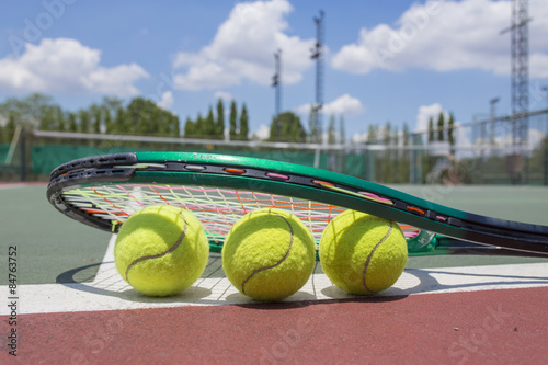 Close up view of tennis racket and balls on the tennis court - 84763752