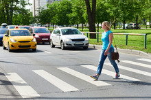 Woman Crossing Street At Pedestrian Crossing
