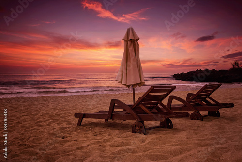Sea sunrise view with two deck chairs and a beach umbrella