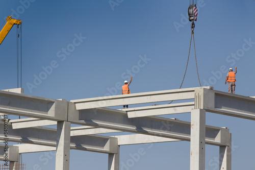 Fotografía  Height worker standing on truss on building skeleton