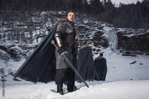 Fotografie, Tablou  Medieval knight with sword in armor in winter rock landscape