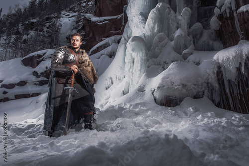 Medieval knight with sword in armor in winter landscape Fototapet