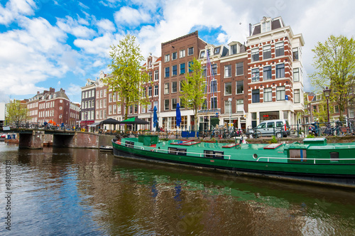 Amsterdam canal with a houseboat along the bank, Netherlands. Wallpaper Mural