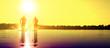 canvas print picture - Glückliche junge Menschen laufen und springen am See beim Sonnenuntergang