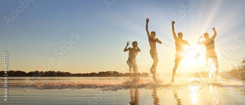 Fototapeta  Glückliche junge Menschen laufen und springen am See beim Sonnenuntergang