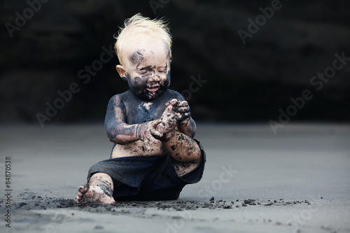 Fotografía  Funny portrait of smiling child with dirty face sitting and playing with fun on black sand sea beach before swimming in ocean