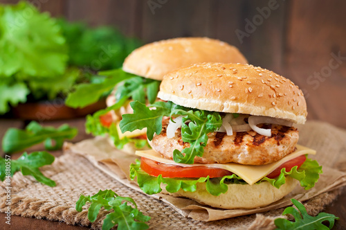 Obraz Sandwich with chicken burger, tomatoes, cheese and lettuce - fototapety do salonu