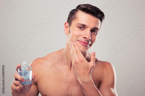 fototapeta na lodówkę Człowiek po goleniu stosowania kremu na twarz