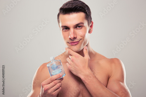 Man applying lotion after shave on face Wallpaper Mural