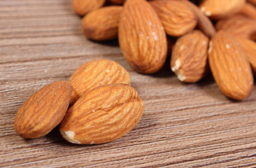 Heap of almonds on wooden background