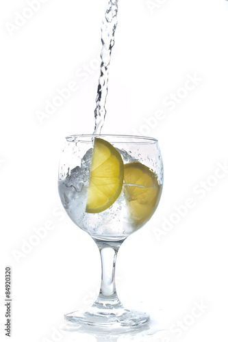 Cocktail with ice and lemon isolated on white background