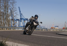 Motorcyclist Riding Along An Asphalt Road