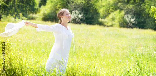 Fotografia  Happy Young Woman Enjoying Summer on the Green Meadow.