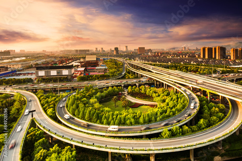 Elevated overpass with skyline of modern city during sunset. Canvas Print