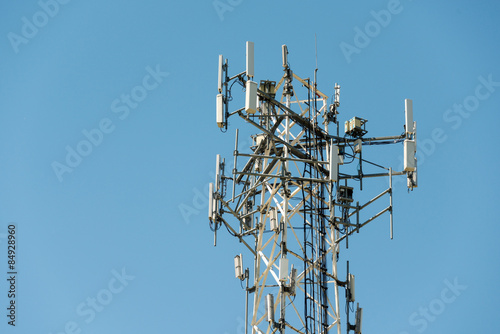 Fotografie, Tablou  Cell phone communication tower with multiple antennas against a blue sky
