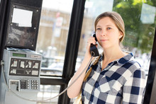 Young Woman Using A Public Phone Box