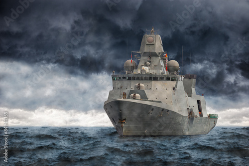 The military ship on sea against heavy clouds. Wallpaper Mural
