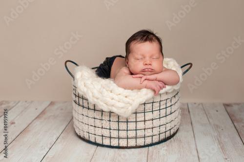 Photo  Newborn Baby Boy Sleeping in a Wire Basket
