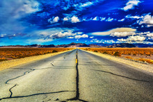 Tar Lines Of An Open, Desert Highway As Clouds Dance On The Horizon Near Death Valley, California