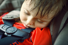Closeup Portrait Of A Cute Adorable Little Boy Toddler Tired And Sleeping Belted In Car Seat On His Trip, Safety Protection Concept
